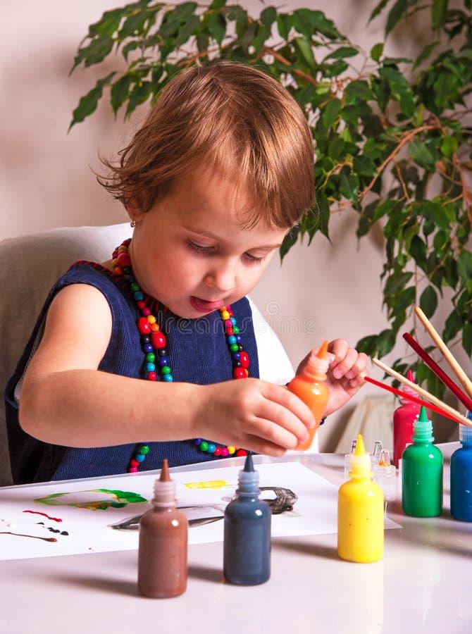 Una niña hermosa dibuja una imagen con las pinturas coloreadas fotos de archivo