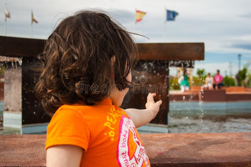 Una niña intenta coger descensos del agua fotografía de archivo