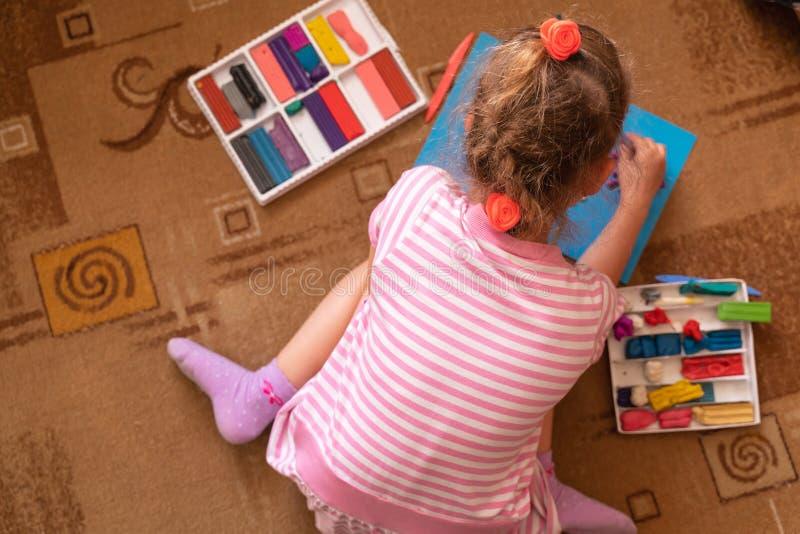 Una niña juega y esculpe de la arcilla modelado del plasticine y el desarrollo de las habilidades de motor finas imagenes de archivo