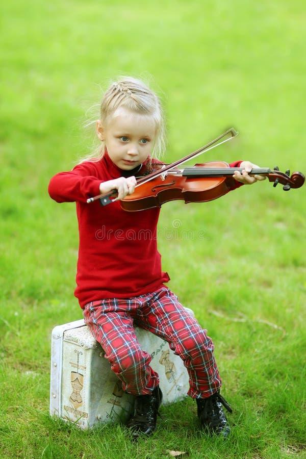 Una niña linda con un violín en el parque imagenes de archivo