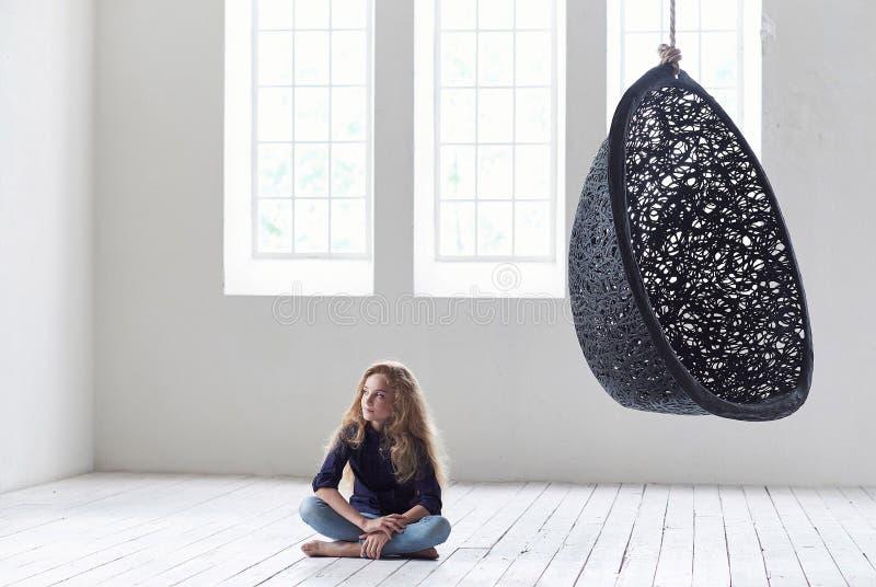 Una niña linda en ropa casual se sienta cerca de una silla suspendida en un estudio vacío fotos de archivo libres de regalías