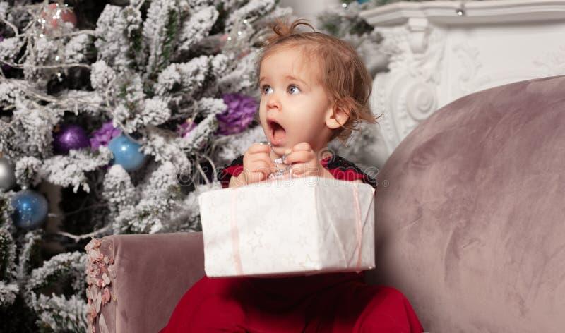 Una niña linda hermosa vestida en un vestido rojo de la tarde elegante se sienta en el sofá y abre un regalo del ` s del Año Nuev imagenes de archivo