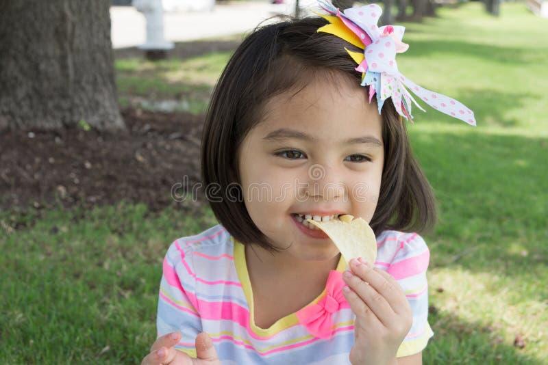 Una niña linda que come microprocesadores mientras que teniendo comida campestre en parque con fotos de archivo libres de regalías