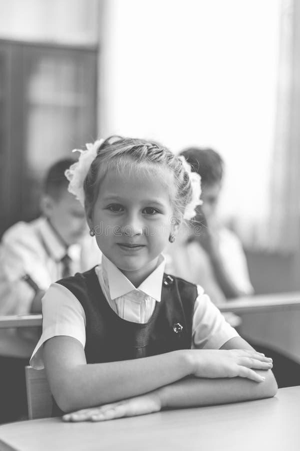 Una niña linda se sienta en el escritorio de la escuela en el primer día escolar imagen de archivo