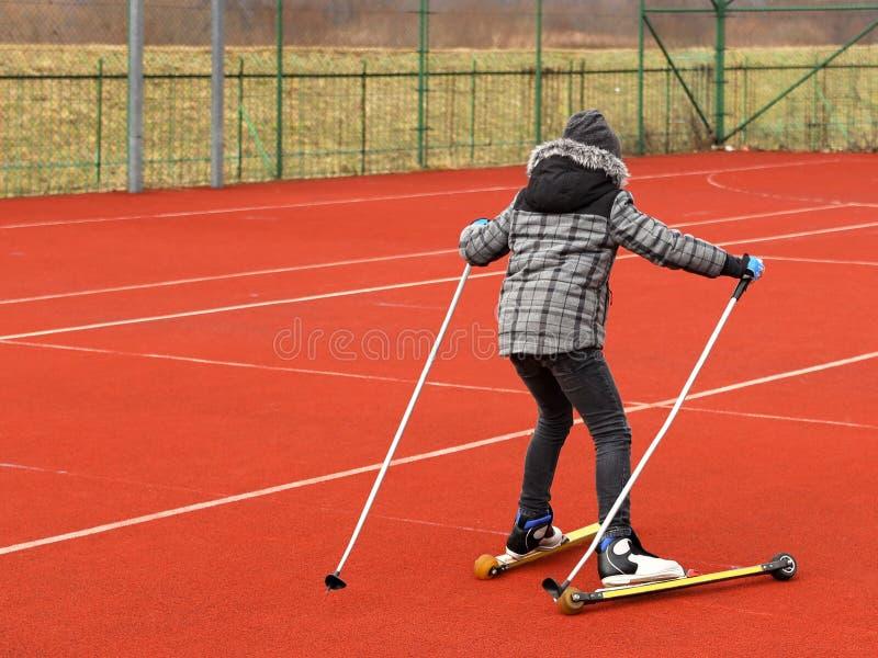 Una niña monta esquí de fondo del entrenamiento del verano con el ro fotografía de archivo libre de regalías