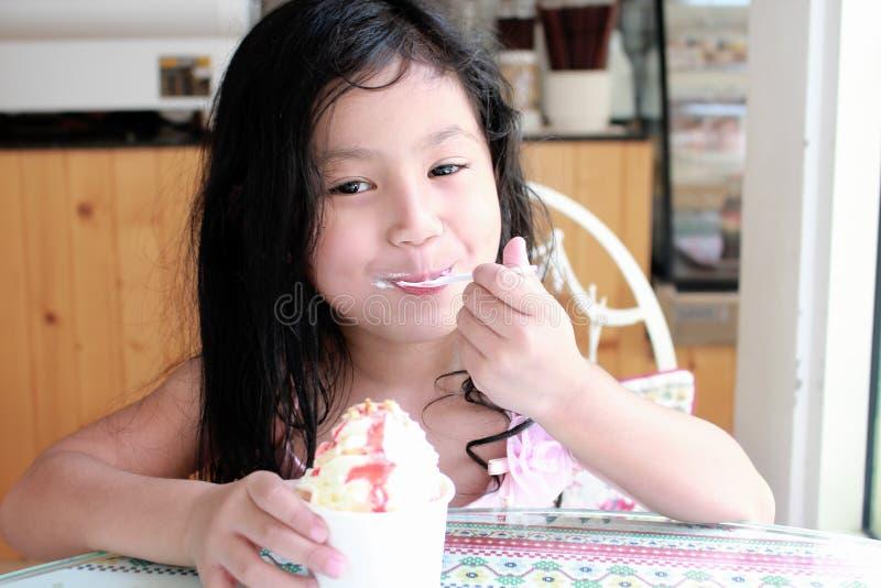Una niña que come el helado fotos de archivo