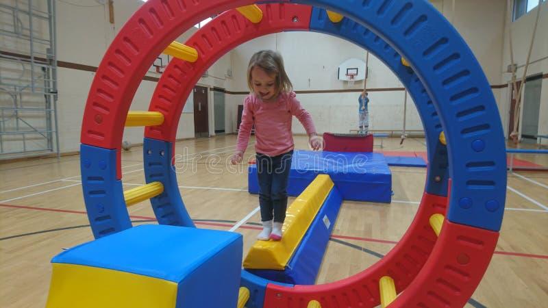 Una niña que equilibra en un haz de la gimnasia que piensa en su próximo paso imagenes de archivo