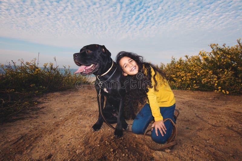 Una niña que juega con su perro casero foto de archivo