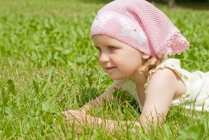 Una niña que miente en un césped verde fotografía de archivo libre de regalías