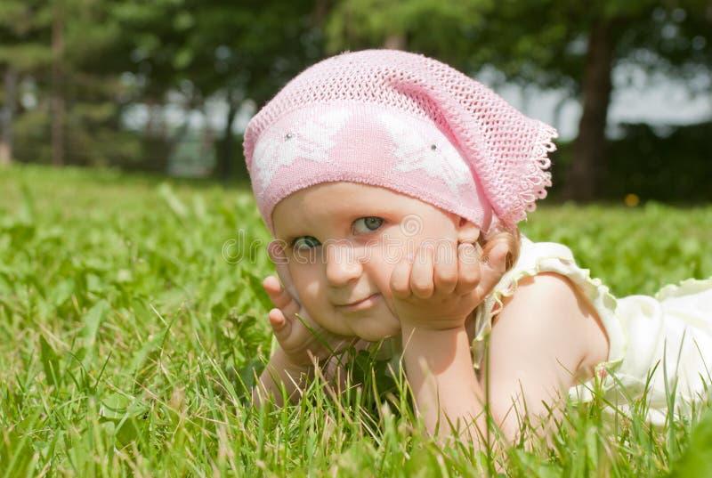 Una niña que miente en un césped verde imagenes de archivo