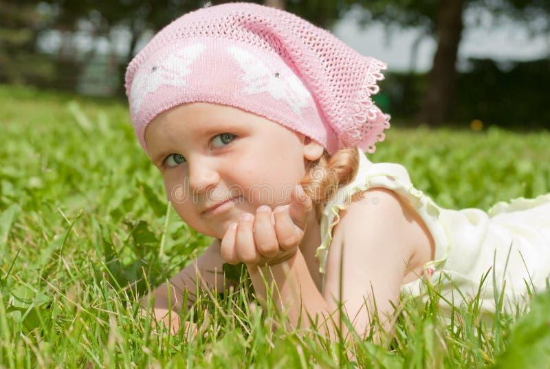 Una niña que miente en un césped verde fotografía de archivo