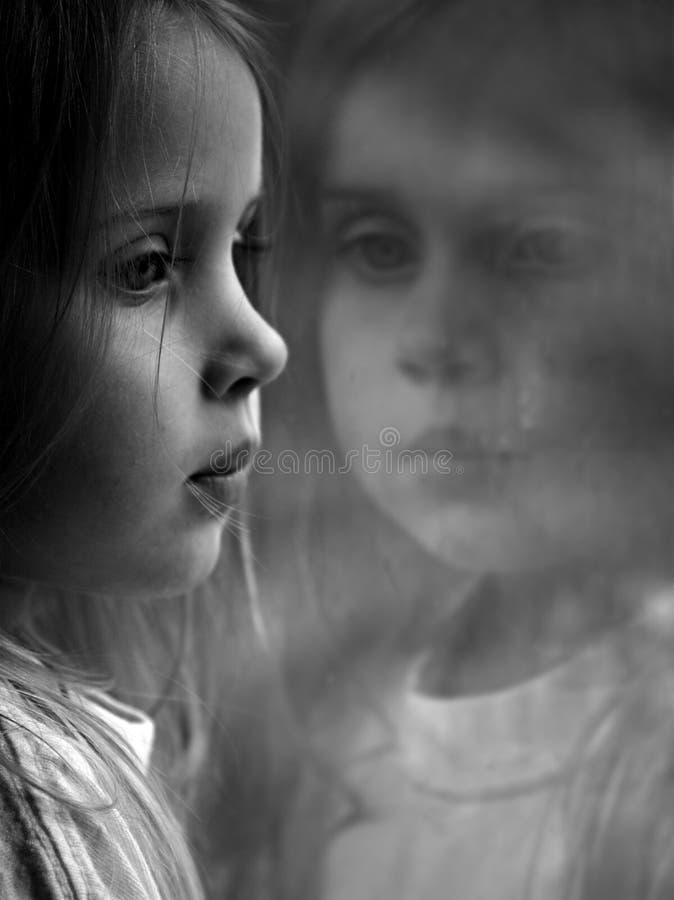 Una niña que mira hacia fuera una ventana fotos de archivo