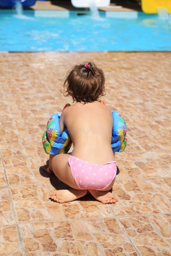 Una niña que se sienta por la piscina imagen de archivo