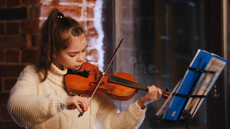Una niña que toca el violín por las notas en el estudio imágenes de archivo libres de regalías