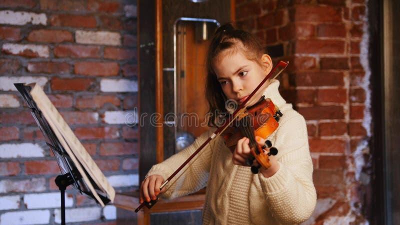 Una niña que toca el violín por las notas imágenes de archivo libres de regalías