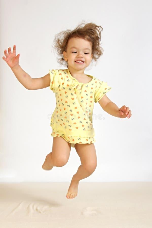 Una niña salta. imagen de archivo