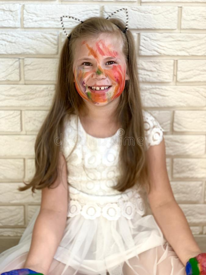Una niña se está divirtiendo, pintura coloreada en sus manos imágenes de archivo libres de regalías