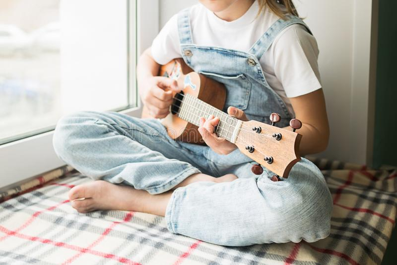 Una niña se está sentando por la ventana en la casa que toca la guitarra Foco selectivo El concepto de m?sica y de arte foto de archivo libre de regalías