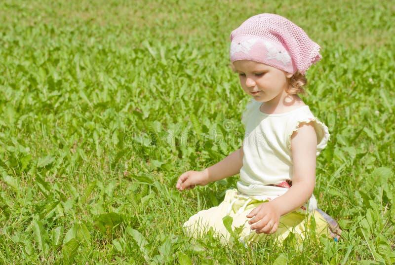Una niña se sienta en un césped verde imagen de archivo libre de regalías