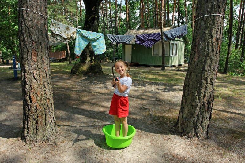 Una niña sonriente con dos trenzas se está colocando en el cuenco del lavadero y está jugando con el arma de agua imagen de archivo
