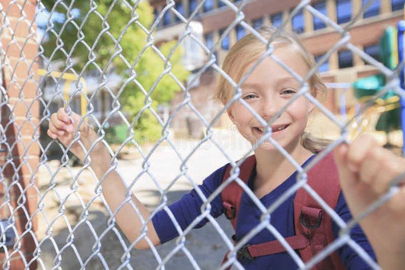 Una niña sonriente en el patio de la escuela foto de archivo libre de regalías