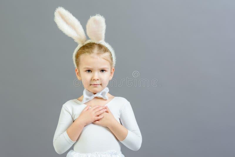 Una niña vestida como conejo blanco dobló sus brazos a través de su espacio de la copia del pecho Foto hermosa con el espacio par foto de archivo libre de regalías