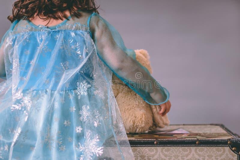 Una niña vestida como princesa sostiene un oso de peluche mientras que se sienta en un pecho fotos de archivo libres de regalías