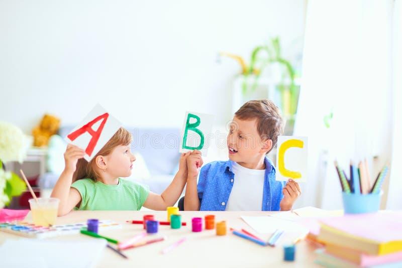Una niña y un muchacho aprender en casa niños felices en la tabla con la sonrisa de las fuentes de escuela divertida y el aprendi imágenes de archivo libres de regalías