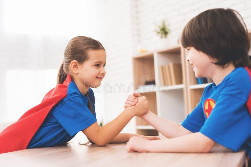 Una niña y un niño pequeño en trajes de super héroes Miden su fuerza en un cuarto brillante fotografía de archivo libre de regalías