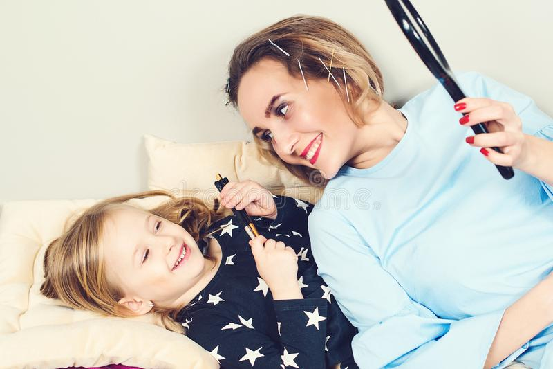 Una niñita linda y su madre están maquillando en casa Mamá e hija divertiéndose juntos, jugando con cosméticos Feliz imagen de archivo