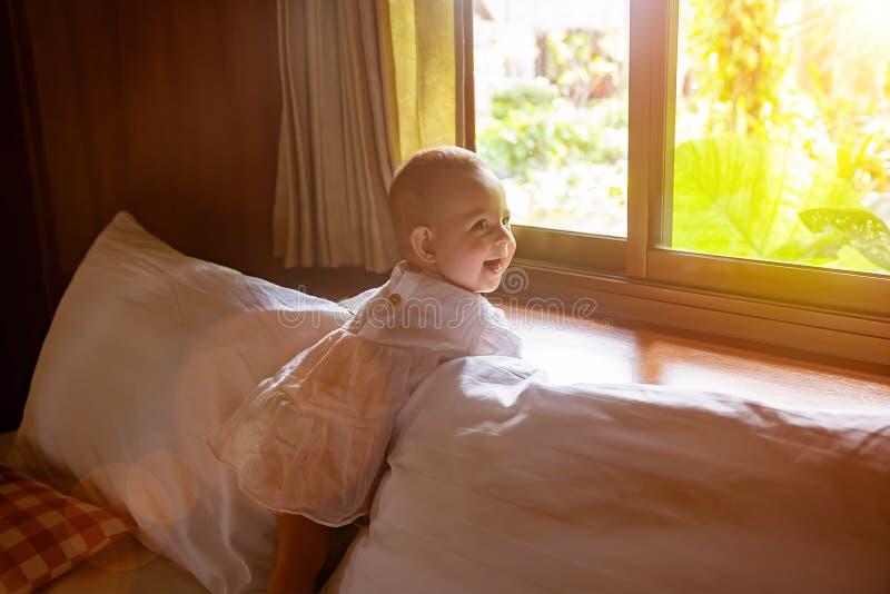 Una ni?a de risa en un vestido blanco se est? colocando en una cama contra la perspectiva de la ventana detr?s de la cual la selv foto de archivo