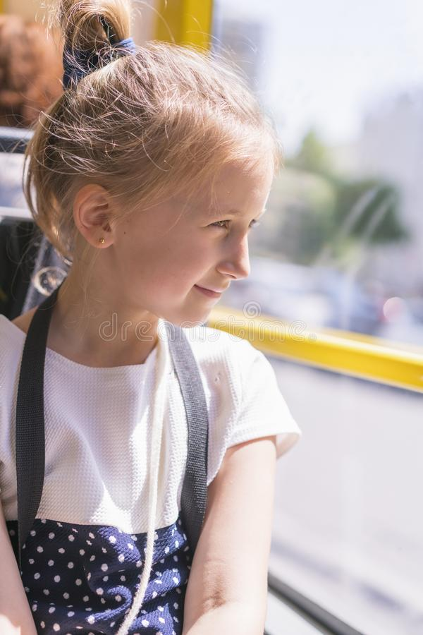Una ni?a va en autob?s La colegiala que se sienta en autob?s escolar y alista para su primer paseo Foto vertical fotos de archivo libres de regalías