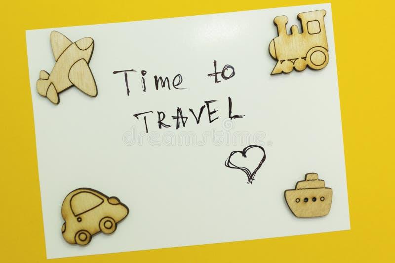 Una nota 'hora de viajar 'con las figuras del transporte en un fondo amarillo imagen de archivo libre de regalías