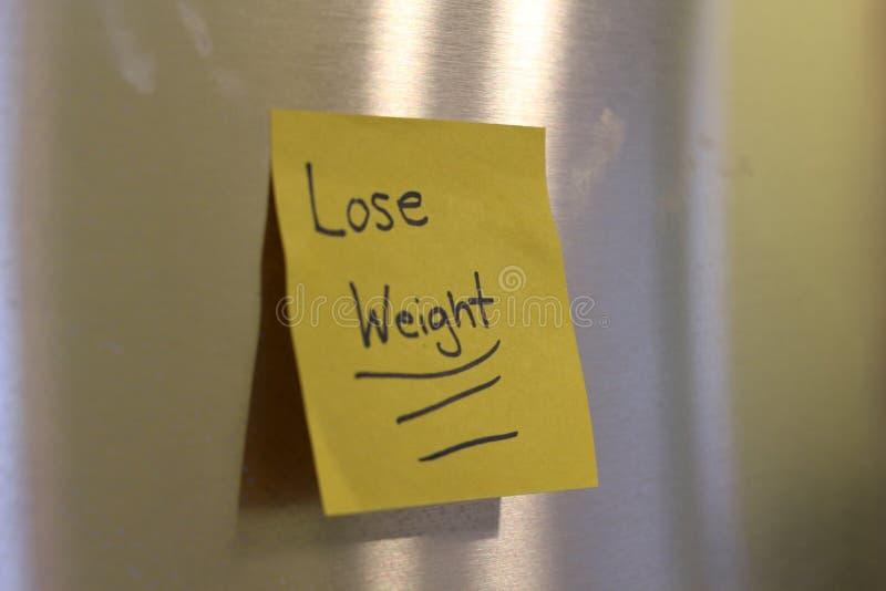 Una nota que dice perder el peso que está pegajoso en el refrigerador imagenes de archivo
