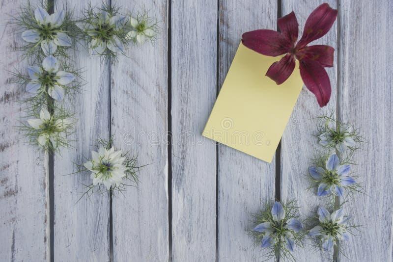 Una nota sobre una superficie de madera enmarcada por las flores 9 imagen de archivo