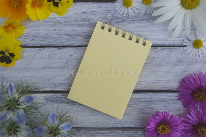 Una nota sobre una superficie de madera enmarcada por las flores 1 del verano fotos de archivo libres de regalías