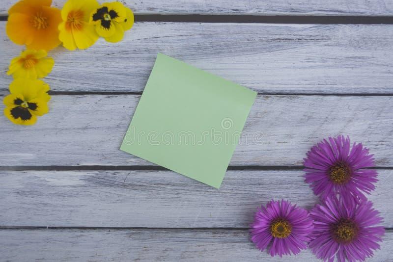 Una nota sobre una superficie de madera enmarcada por las flores 2 del verano fotos de archivo