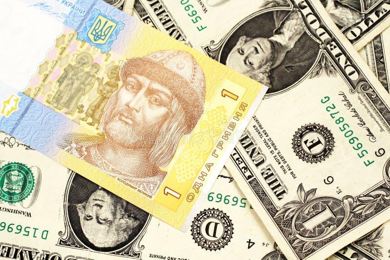 Una nota ucraniana del hryvnia con los billetes de dólar del americano uno fotos de archivo