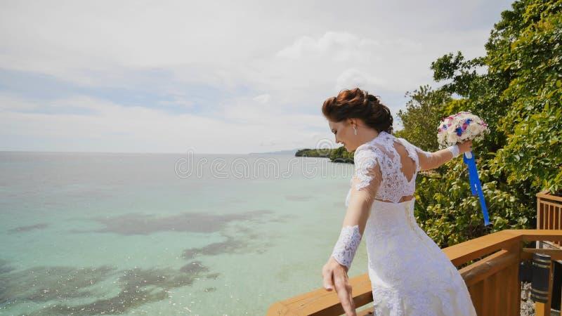 Una novia de deslumbramiento disfruta de felicidad de la altura del balcón que pasa por alto el océano y los filones Vuelo del am foto de archivo