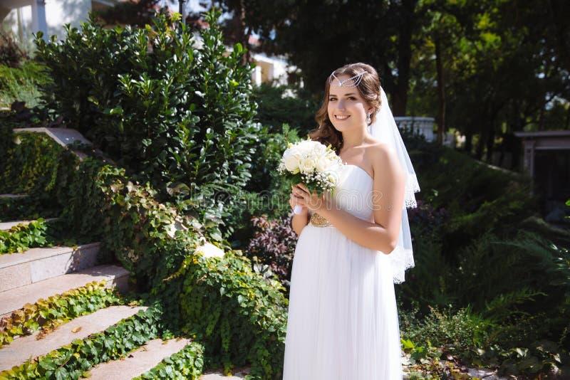 Una novia embarazada de la clase europea presenta con un ramo de rosas blancas, organizado una boda en el estilo griego fotografía de archivo