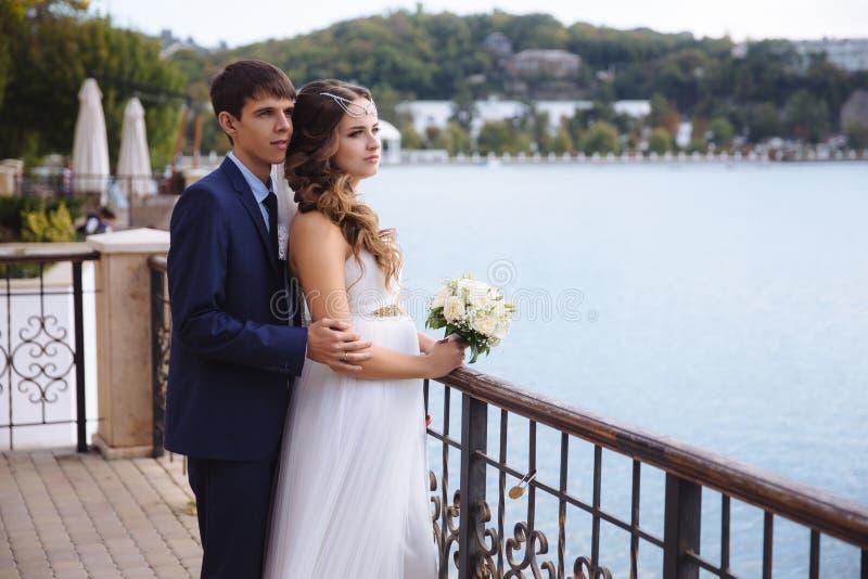 Una novia embarazada en un vestido de boda se está colocando en el muelle, admirando la vista del río, detrás de sus abrazos su m foto de archivo