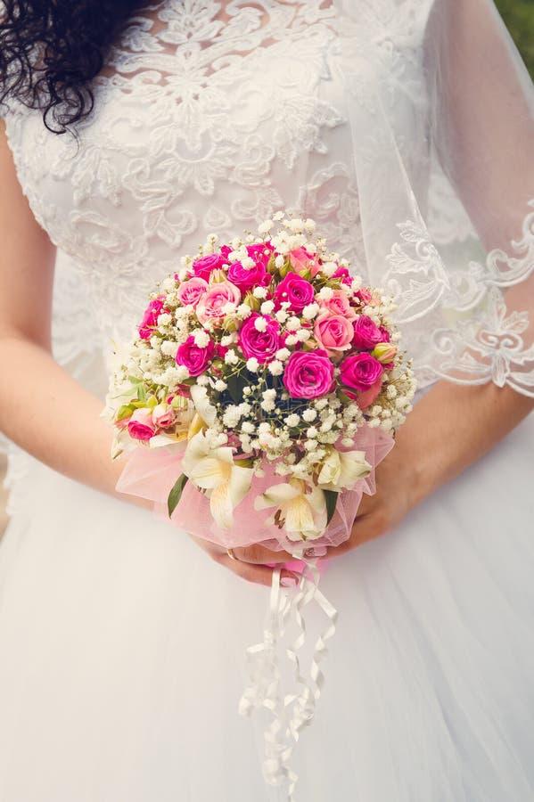 Una novia en un vestido que se casa blanco está sosteniendo un ramo en sus manos Primer, foco selectivo Tono en el estilo de inst fotos de archivo