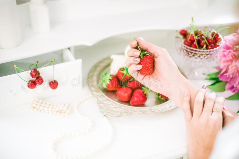 Una novia hermosa está sosteniendo una fresa en sus manos que se sientan en un tocador con un espejo, un ramo de peonías imágenes de archivo libres de regalías