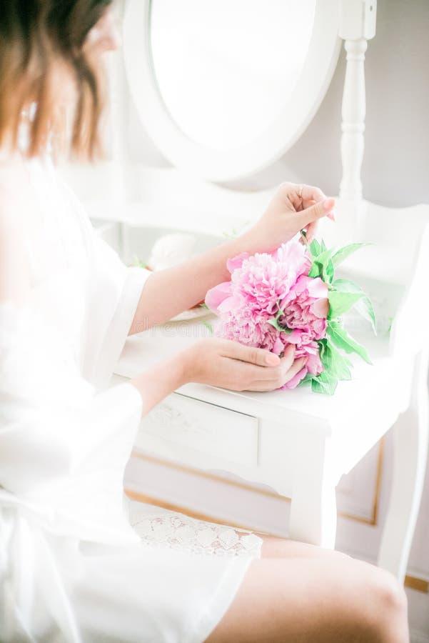 Una novia hermosa está sosteniendo las peonías en sus manos que se sientan en un tocador blanco con un espejo, collar de la perla fotografía de archivo