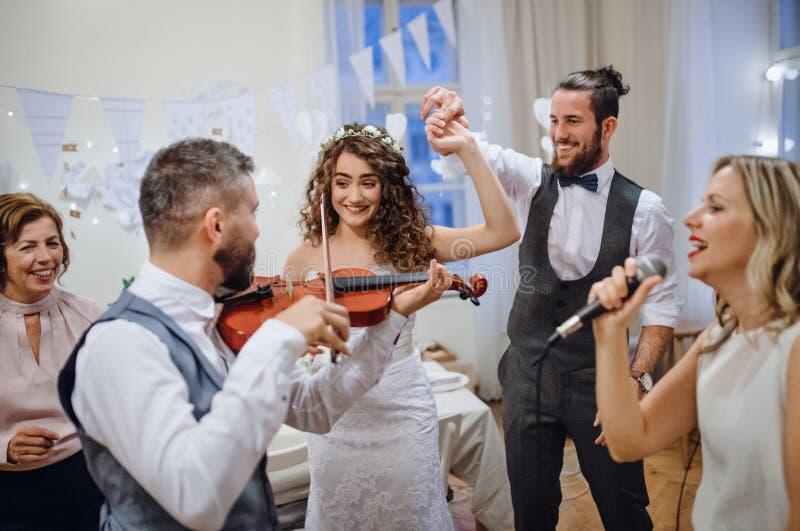 Una novia joven, novio y otras huéspedes bailando y cantando en una recepción nupcial imágenes de archivo libres de regalías