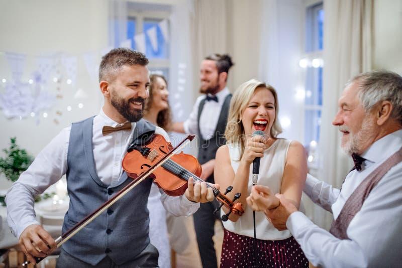 Una novia joven, novio y otras huéspedes bailando y cantando en una recepción nupcial fotografía de archivo libre de regalías