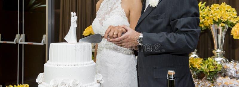 Una novia y un novio está cortando su pastel de bodas fotos de archivo