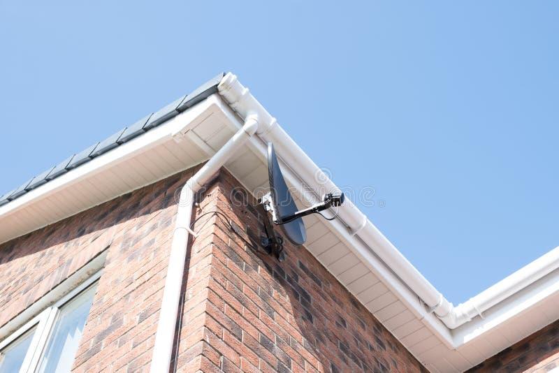 Una nueva antena parabólica instalada en el lado de un edificio residencial fotografía de archivo