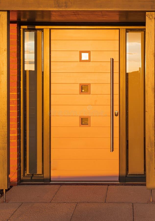 Una nueva puerta principal moderna del apartamento tomada durante una puesta del sol muy baja, brillante y amarilla fotografía de archivo libre de regalías