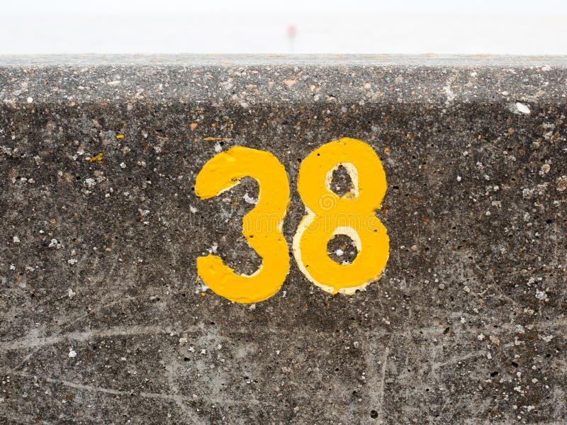 Una numerazione gialla con la pittura sulla parete anteriore Harwich 38 del mare immagine stock libera da diritti